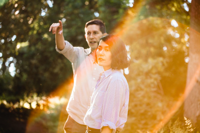 couple in forest with lens flare